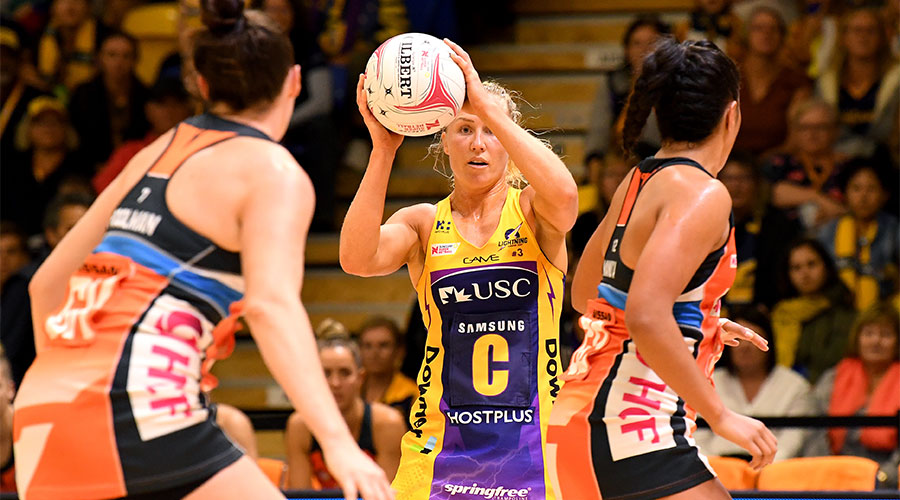 Laura Langman passing the ball surrounded by Giants players