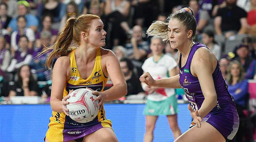 Steph Wood looking to pass the ball with Kim Jenner defending